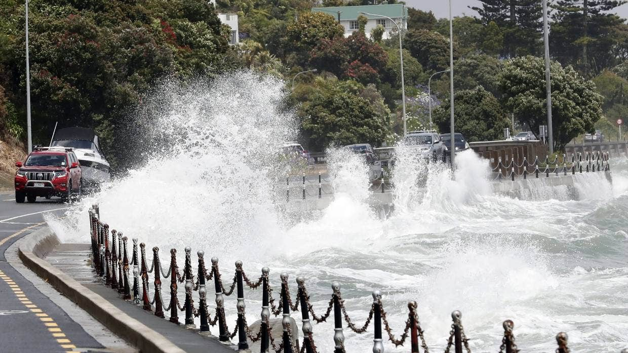 Waves at high tide splash over the footpath and onto Rocks Rd, Nelson